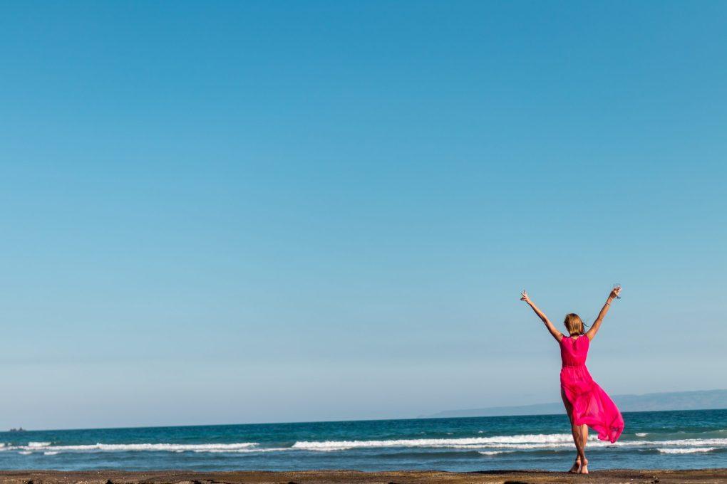 ragazza con vestito rosa in spiaggia