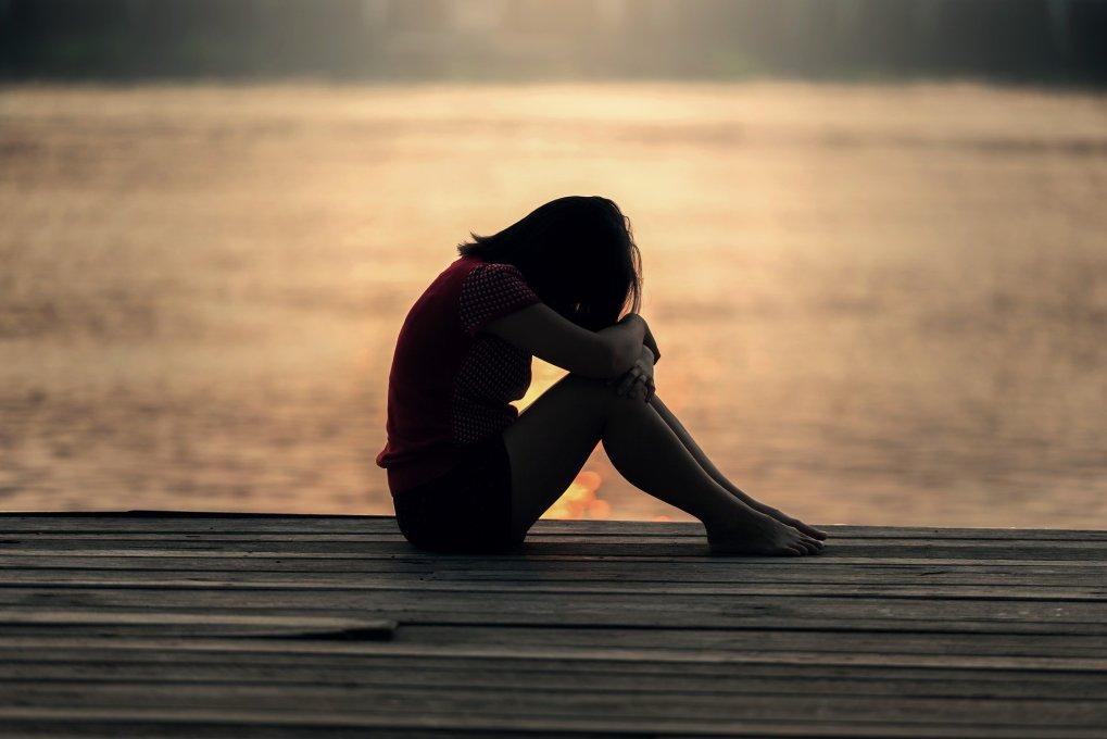 ragazza triste in ombra spiaggia tramonto