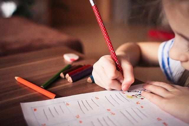 regali utili da fare durante il covid immagine bambina che studia con quaderno e matite colorate