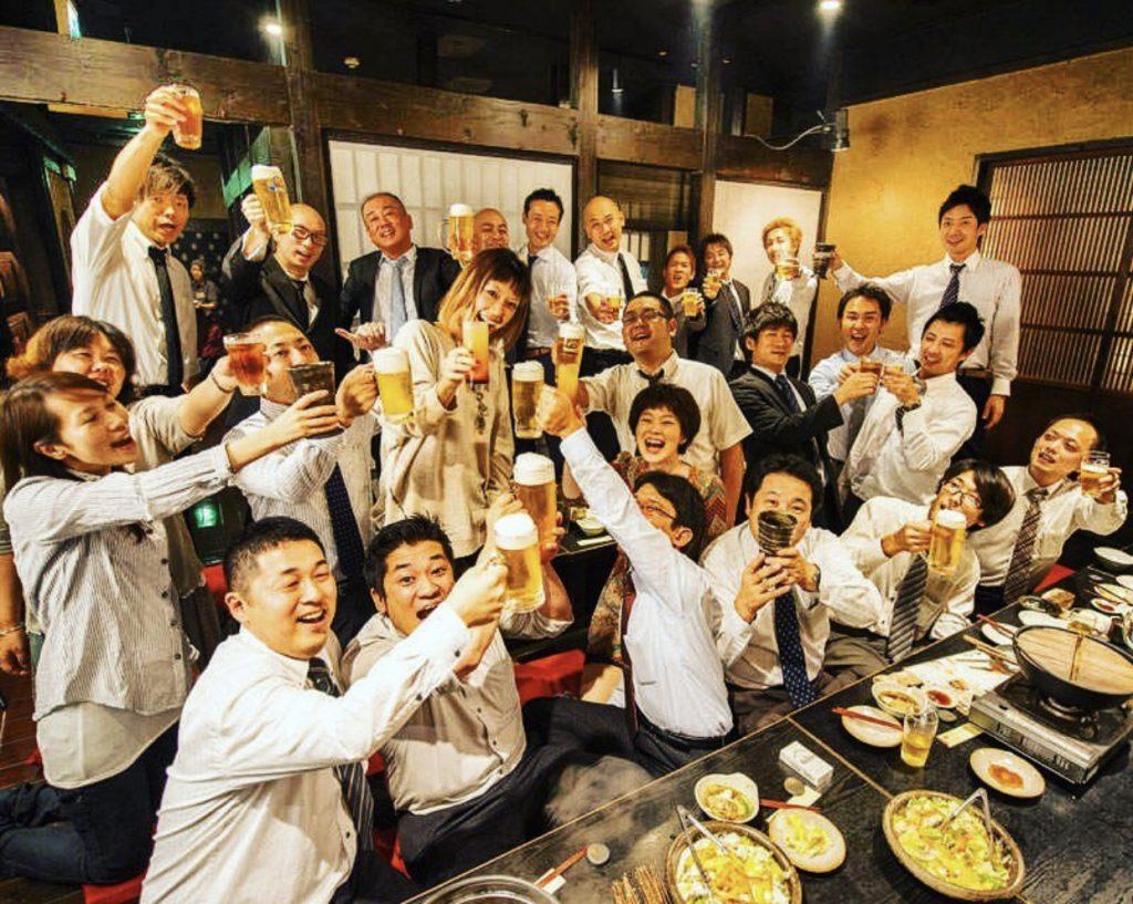 gruppo di giapponesi che brindano con bicchieri di birra