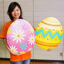 ragazza giapponese con due uova giganti colorate in mano