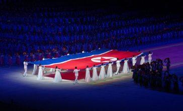 bandiera corea del nord retta da partecipanti manifestazione La Corea del Nord non parteciperà alle Olimpiadi