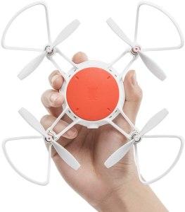 drone xiaomi MITU, piccolo drone che si può tenere in mano come nell'immagine di colore bianco e con un cerchio in mezzo arancione