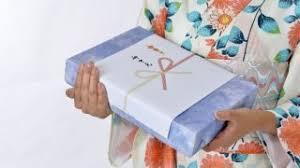 mani di donna in kimono con regalo ochugen in un macchetto dalla carta viola e bianca ochugen il mio viaggio in giappone traveltherapists