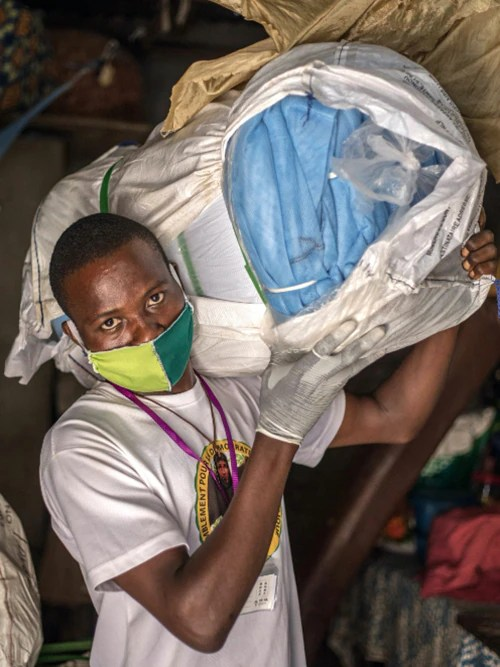 Agent Jean Kinhouande distributes mosquito nets in the Agla district of Cotonou, Benin, to fight malaria despite the COVID-19 pandemic disruption. (Photo by Yanick Folly/AFP via Getty Images, April 28, 2020)