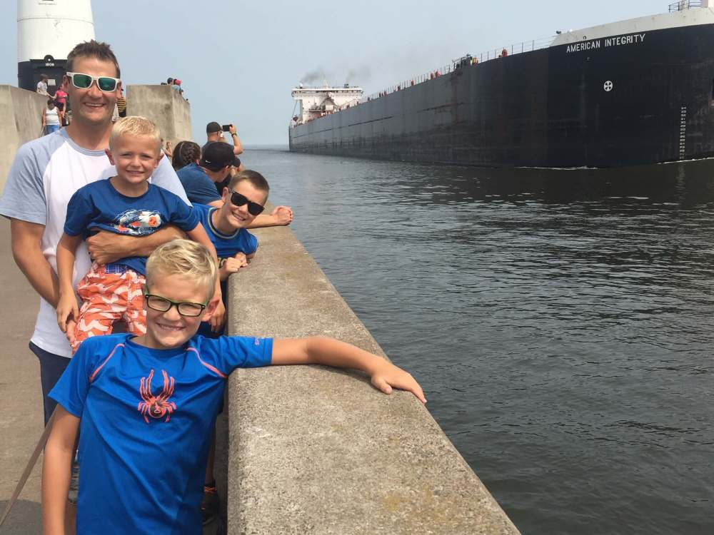 The Best Things to Do in Duluth MN with your Family featured by top US family travel blog, Travel with a Plan: image of a Family leaning over railing at Duluth port
