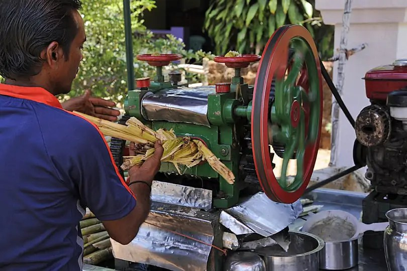Squeezing sugar cane to produce a refreshing drink in Goa
