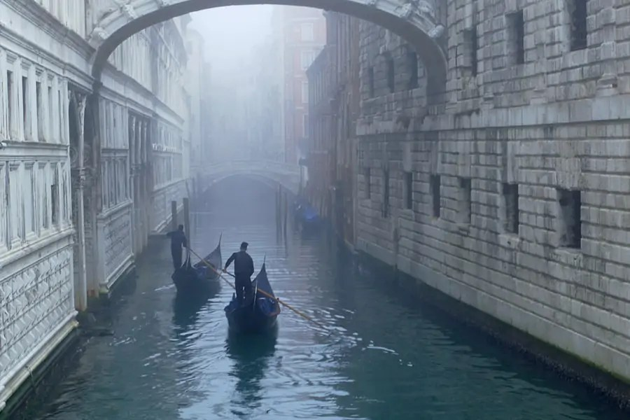 Gondolas disappearing into the mists under the Bridge of Sighs, Venice, taly