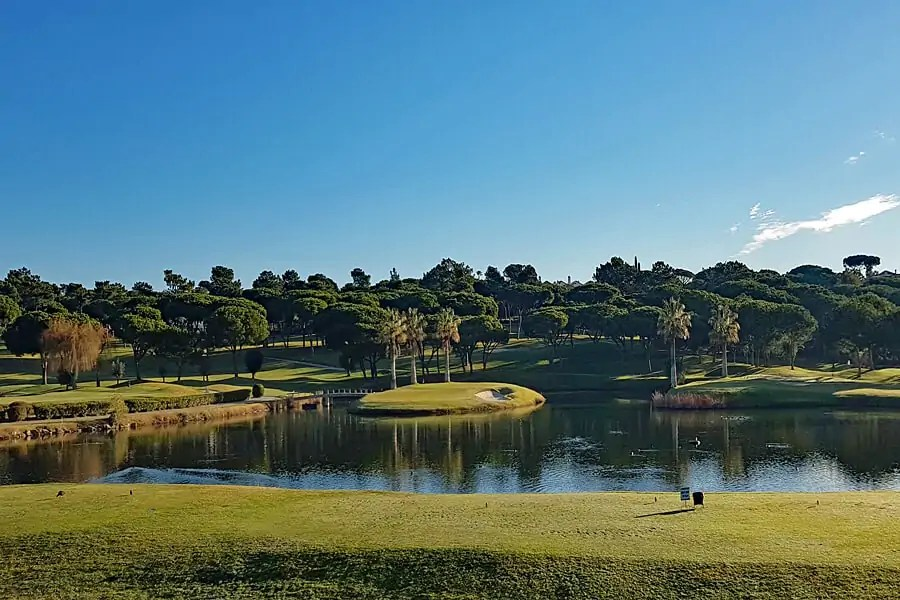 The pristine green fairways and lakes of one of three championship golf course in Quinta do Lago, Algarve, Portugal