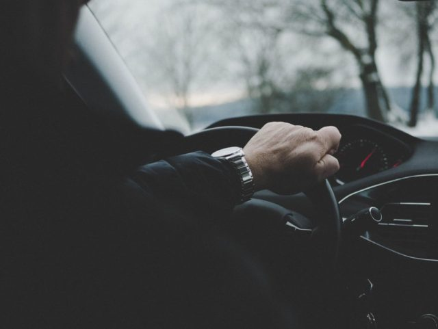 A man's hand grips the steering wheel of a car as he drives.