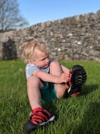 child putting on sandal