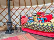 Day deb and log burner inside yurt with two children