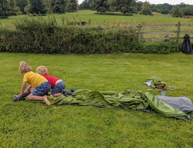two boys rolling out a tent