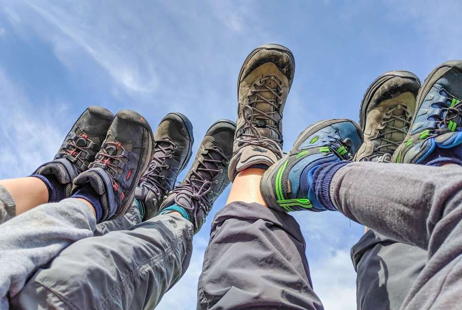family hiking boots in the air