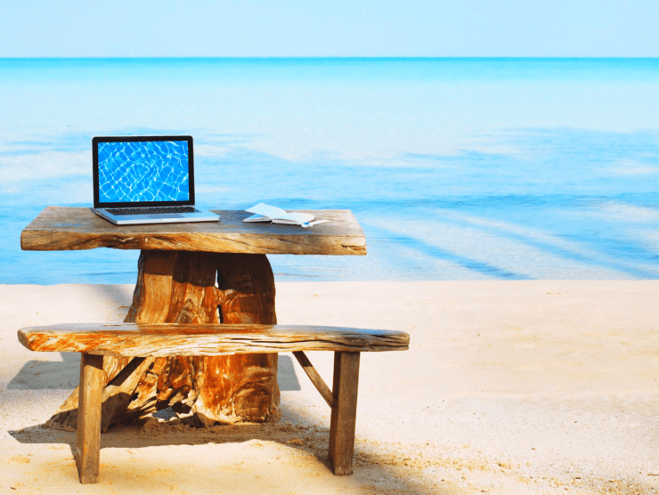 Computer sitting on table on the beach