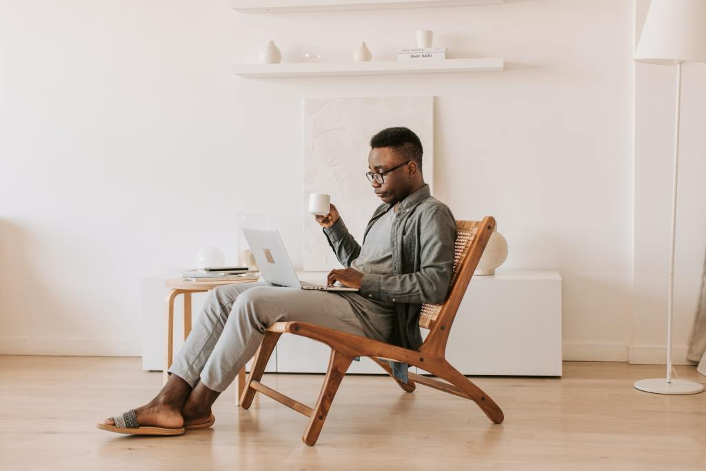 Man remote work sitting with a coffee cup and laptop
