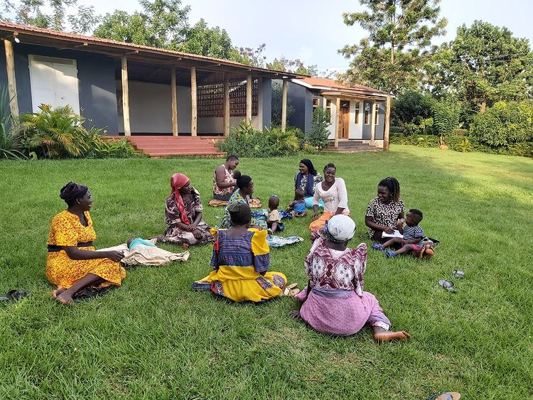 Group of Ugandan girls and women sitting on grass talking and laughing at Tusubira Village.