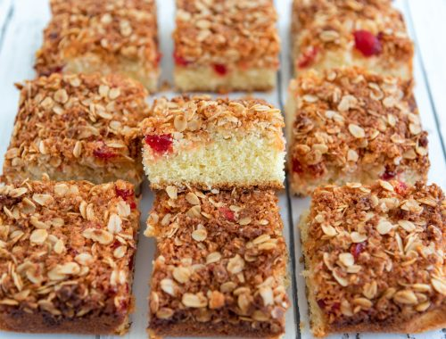 Base layer of cake topped with an oat, coconut and cherry layer