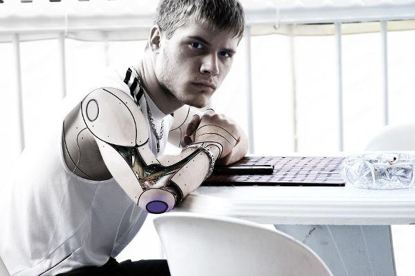 Person halb Mensch halb Cyberwesen am Tisch