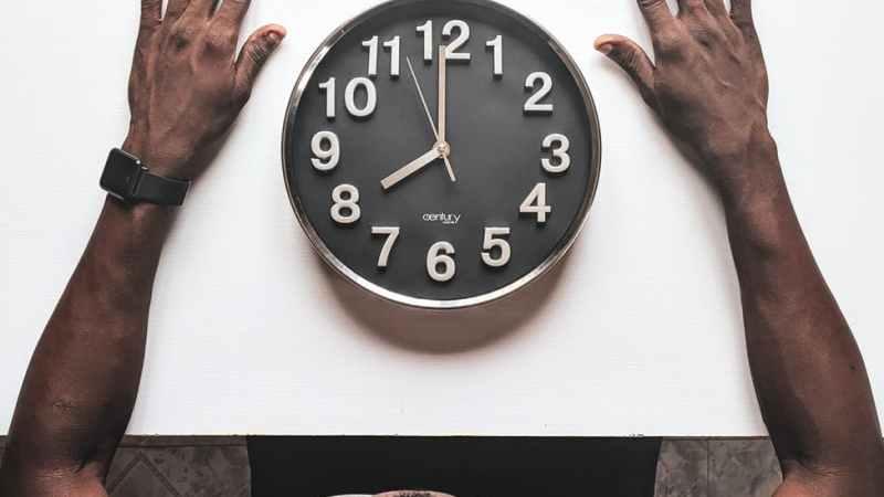 Mann schaut auf die Uhr, die auf dem Tisch liegt und 8 Uhr anzeigt.