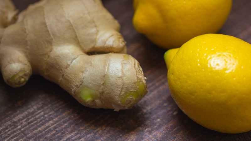 Ingwerknolle neben zwei Zitronen auf dem Tisch.