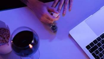 Frau lackiert sich am Schreibtisch die Finger..