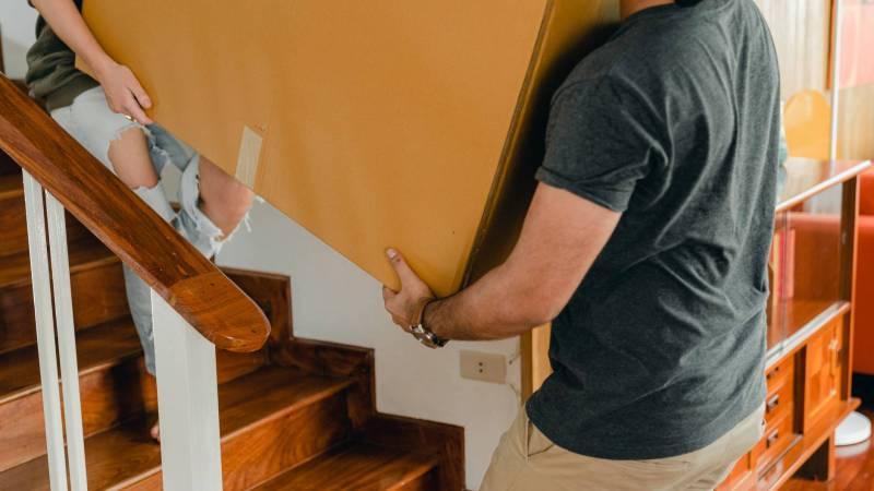 Umzugskarton durchs Treppenhaus tragen.