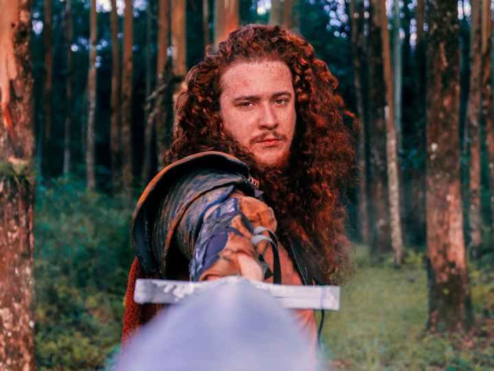 Mann mit gezogenem Schwert im Wald.