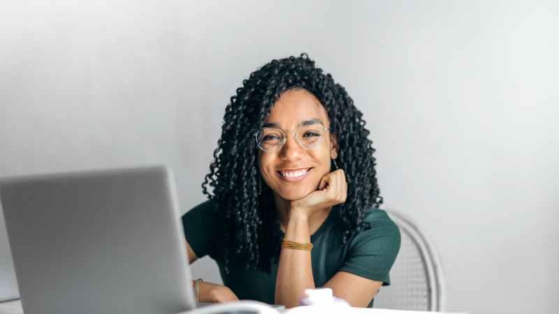 Frau am Rechner lächelt.