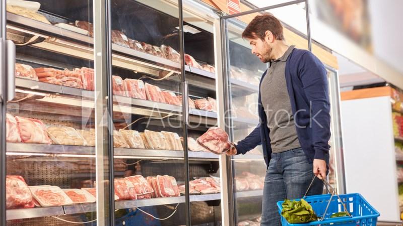Junger Mann am Gefrierschrank beim Fleisch Kauf