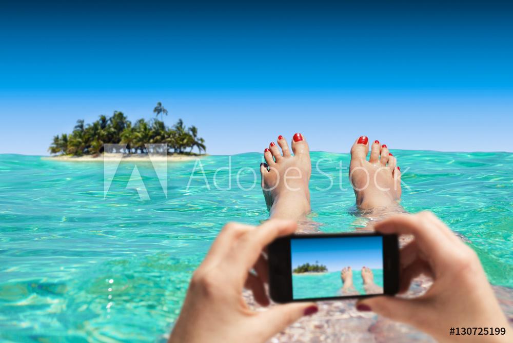 Frau macht Foto mit Smartphone im Urlaub