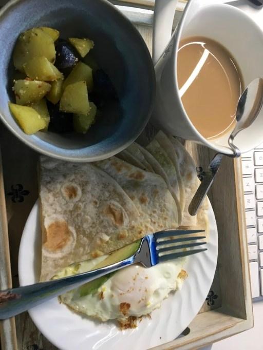 Eggs and avocado quesadilla, potatoes and coffee