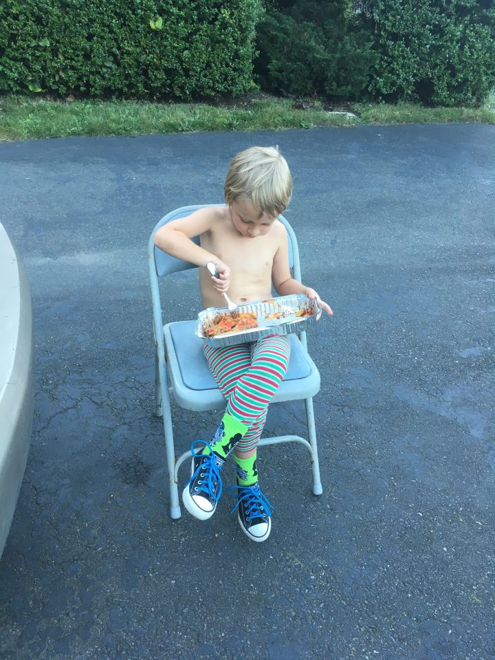 Child sitting in a chair eating dinner outside