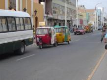 Street in Pisco with buses, cars and mototaxis.