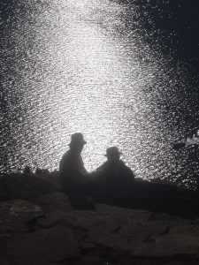 The silhouette of two Bolivian men sitting on Isla del Sol with the reflection of the sun shinning off of Lake Titicaca.