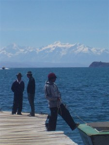Bolivian man tying up the boat in Lake Titicaca with beautiful snow capped mountains in the background.