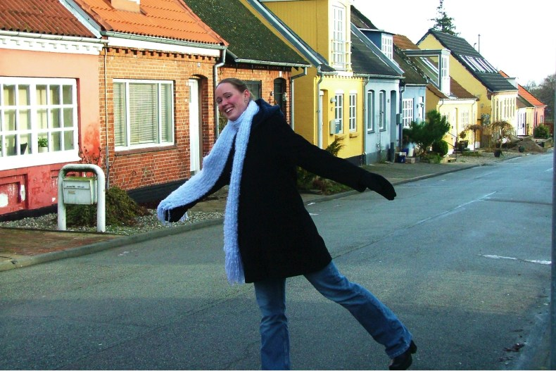 Sarah Beth dancing on a street with colorful houses in Kolding, Denmark.