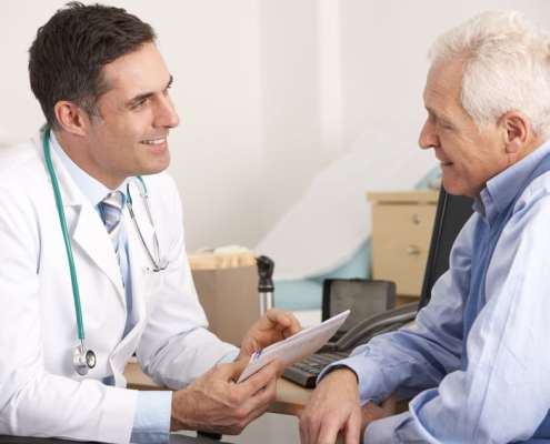 radiation oncologist talking to a senior man prior to treatment