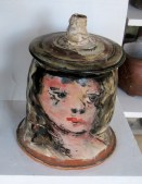 A lidded jar with woman's head.