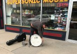 """Here's a little experiment: """"Can you make a shallow, light bass drum with backpack straps that I could play on the sidewalk when I busk with my guitar?"""" This is what we came up with--couple of features include 1¼"""" hoop, folding spurs, canted snare lugs, audience-side tom hoop, prototype """"raw"""" finish. 7¾x20; plied maple; raw maple finish."""