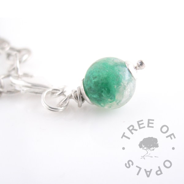 lock of hair pearl lobster claw dangle charm with bottle green shimmer powder showing white hair which is translucent and not visible, so the shimmer is swirled round for texture