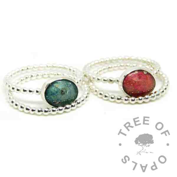 red and teal ashes ring duo, dragon's blood red and mermaid teal resin sparkle mixes, bubble wire Argentium silver bands. Shown with bubble wire slim stacking bands