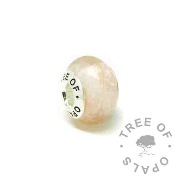 breastmilk bead with subtle fairy pink resin sparkle mix and tiny blonde first curl. Tree of Opals core