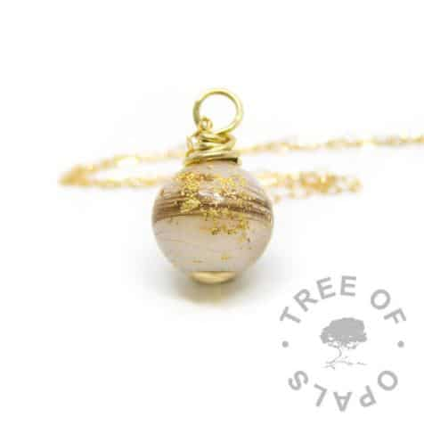 Solid yellow gold breastmilk orb with first curl and gold leaf and lightweight solid yellow gold chain. Golden boobies one year breastfeeding award