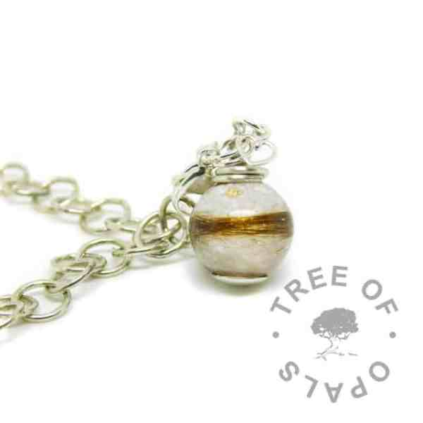 silver breastmilk orb dangle charm with unicorn white resin sparkle mix and baby's first curl. Lobster clasp setting for Thomas Sabo style bracelets, shown on a large link bracelet