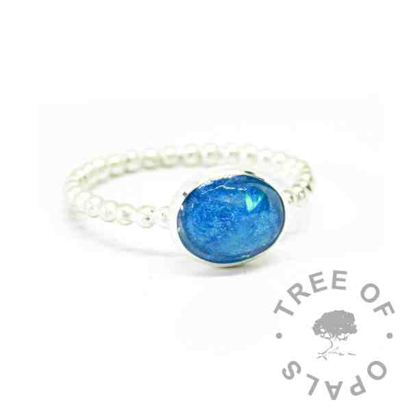 Hair ring on bubble band with Aegean blue and unicorn white resin sparkle mixes combined. White hair not visible in resin (translucent)