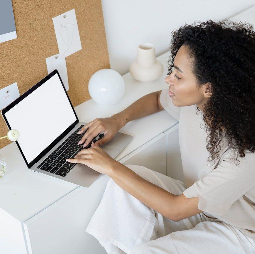 woman in white shirt using macbook pro