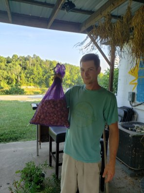 Daniel, My neighbor down the road, holding a bit of his Egyptian Walking Onion Harvest dried at the lake