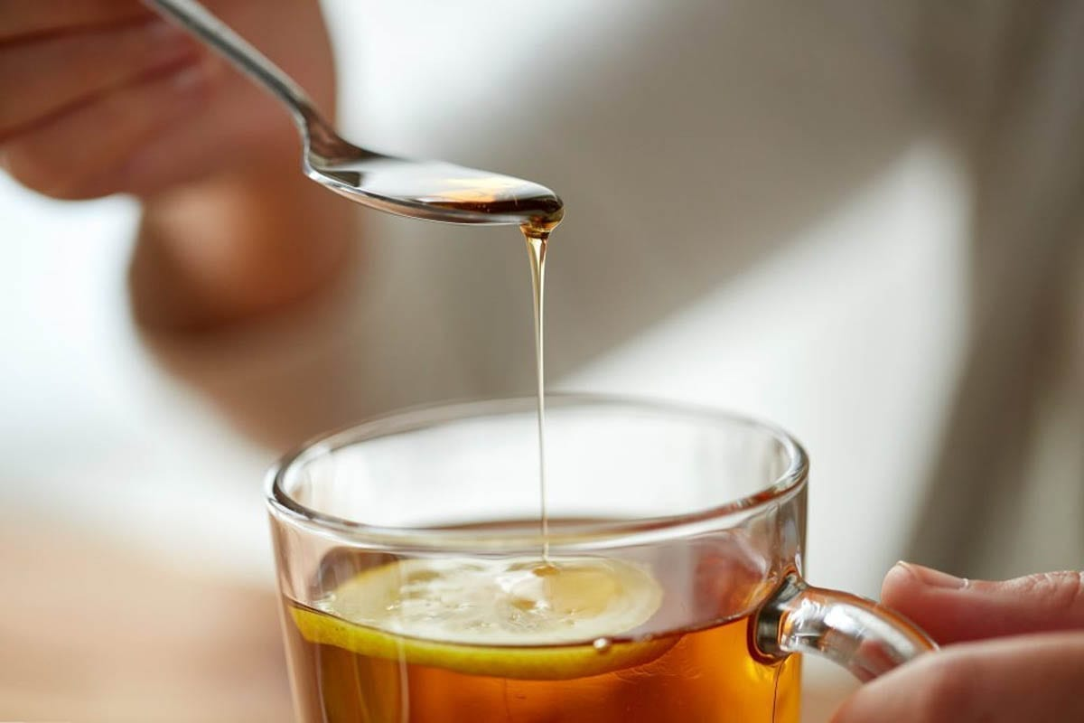 Honey being poured in to an Earl Grey and Lavender Tea cocktail