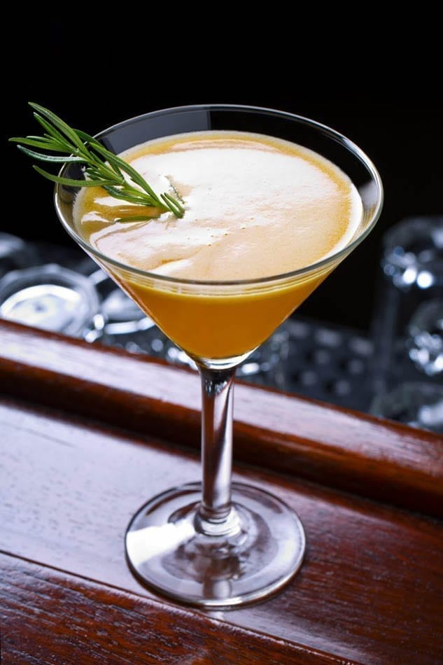 3 French Hens Lemon and Orange Non-Alcoholic cocktail garnished with a rosemary sprig